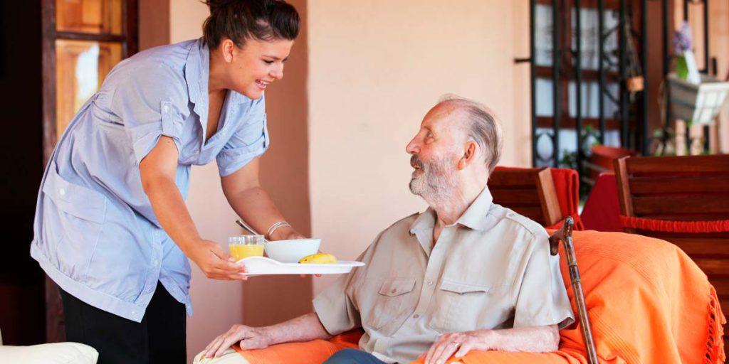 Une préposée servant un repas à une personne âgée